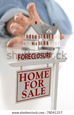 Foreclosure Real Estate Sign in Front of Woman's Hand Reaching for Model House on a White Surface. - stock photo