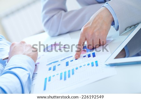 Forefinger of businesswoman pointing at chart of financial document - stock photo
