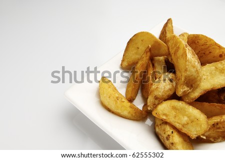 forefront of a fried potato slices on a white plate - stock photo