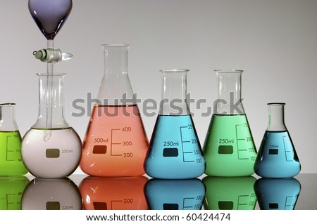 forefront of a laboratory flasks containing brightly colored liquid - stock photo