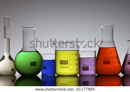 forefront of a laboratory flasks filled with colored liquid