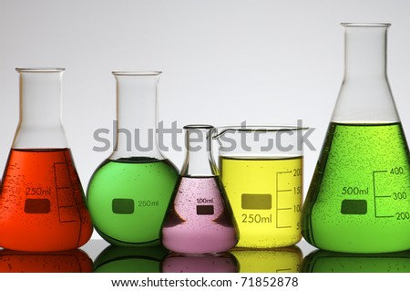 forefront of a laboratory flasks filled with colored liquid - stock photo