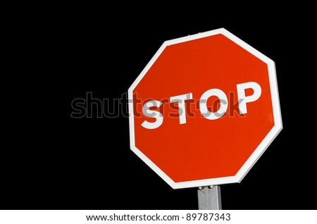 forefront of a stop sign with a black sky - stock photo