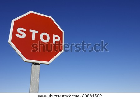 forefront of a stop sign with a clear blue sky - stock photo