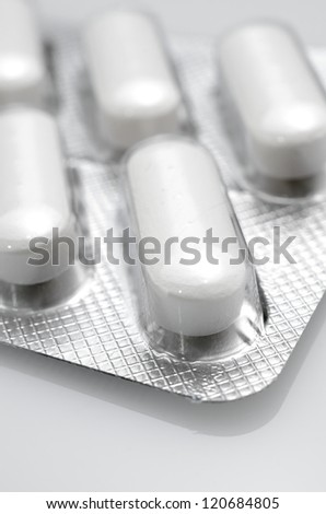forefront of a white medicine pills in blister pack - stock photo