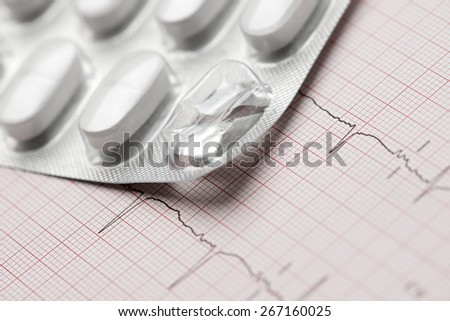 Forefront of a white medicine pills in blister pack and electrocardiogram. - stock photo