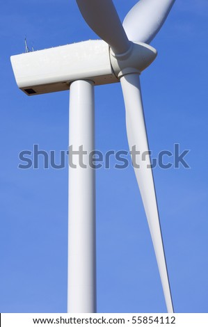 forefront of the propeller of a windmill with blue sky - stock photo
