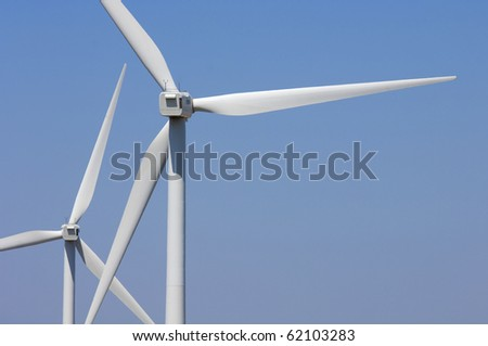 forefront of two windmills for renewable electric energy production - stock photo