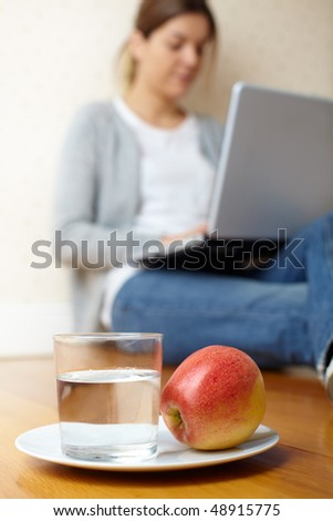 foreground glass of water and apple with out of focus girl in the background - stock photo