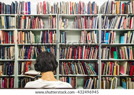 Foreground Man read book in the library shelves - stock photo