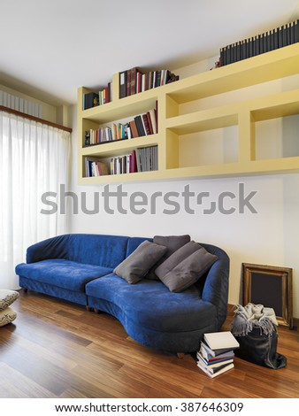 foreground of a blue fabric sofa in the modern living room with masonry bookcase and wood floor - stock photo