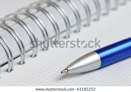 foreground of a pen and a spiral notebook - stock photo