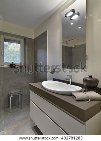 foreground of a washbasin in the modern bathroom overlooking on the shower cubicle - stock photo