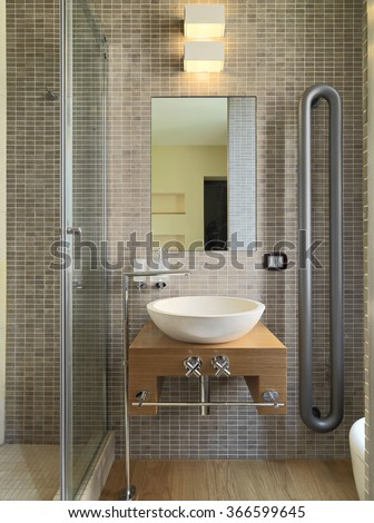 foreground of a washbasin on the wood worktop whose wall is coated of mosaic tiles in a modern bathroom