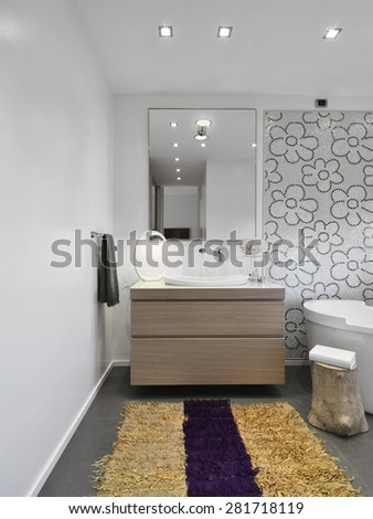 foreground of wood furniture and yellow carpet in the modern bathroom - stock photo