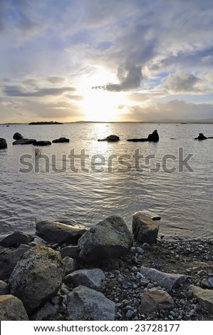 foreground rocks and evening sunlight show peaceful scene at Lough Conn, Co.Mayo, Ireland