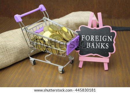 FOREIGN BANK word in mini blackboard with gold coins in wooden table. - stock photo