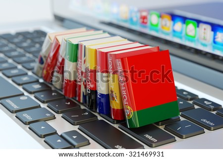 Foreign languages learn and translate education concept, books with covers in colors of national flags of world countries on computer laptop keyboard - stock photo