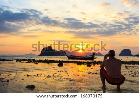 foreigner photograph on beach in morning and sunrise at Trang ,Thailand - stock photo