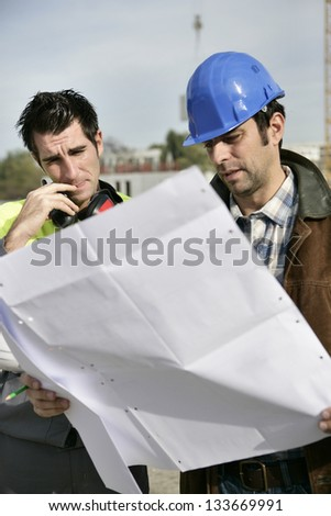 Foreman and colleague checking over plans - stock photo