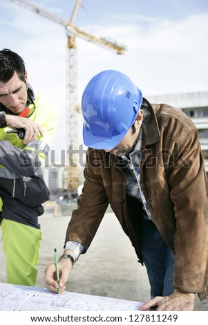 Foreman and colleague working on site - stock photo