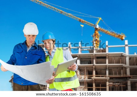 Foreman and engineer with blueprints at construction site