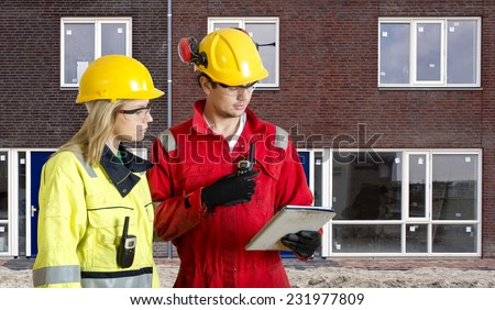 Foreman and real estate development manager going over an electronic checklist during the delivery and completion of a new housing development, constructed from prefab elements - stock photo