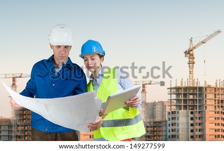 Foreman and student with blueprints at construction site - stock photo