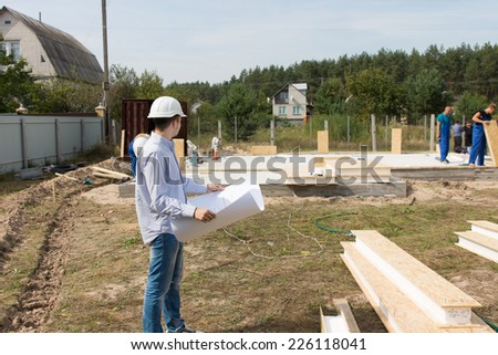 Foreman checking building supplies on site standing in front of a stack of lumber and timber with a blueprint in his hands watching workmen working - stock photo
