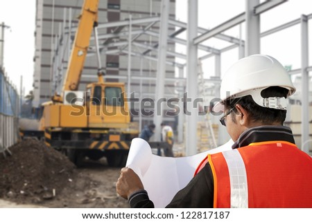 foreman checking plant on construction site with worker background and excavator