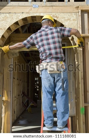 Foreman examining with measure tape - stock photo