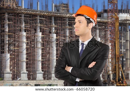 Foreman in a black suit standing with a construction site in the background