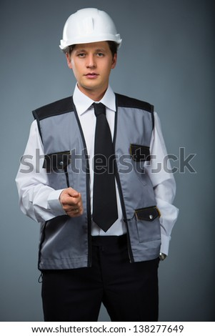 foreman in a blue vest, helmet in hand pocket - stock photo