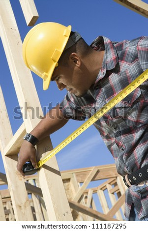 Foreman measuring framework with measure tape at construction site - stock photo