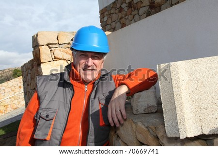 Foreman standing in front of house under construction - stock photo