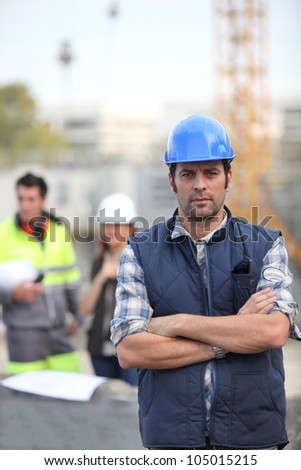 Foreman stood in front of two colleagues - stock photo