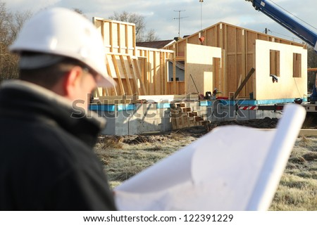 foreman turning his back to camera consulting blueprints in construction site - stock photo