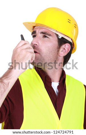 Foreman using radio receiver to delegate work - stock photo