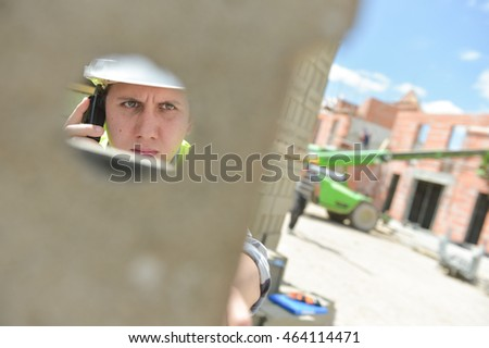 Foreman using walkie-talkie on construction site through a cinderblock