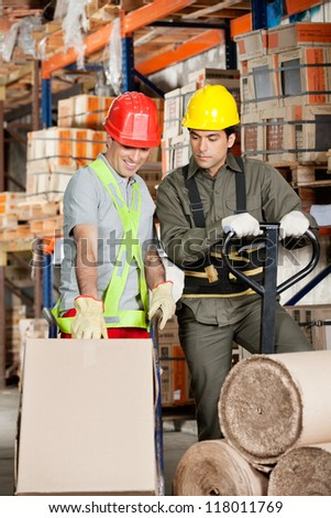 Foreman with handtruck showing something to coworker at warehouse - stock photo