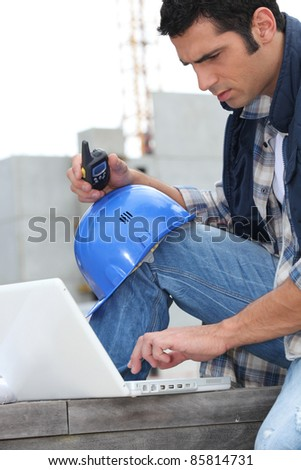 Foreman with radio and computer - stock photo