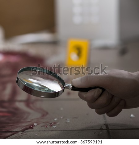 Forensic scientist looking blood through magnifying glass - stock photo