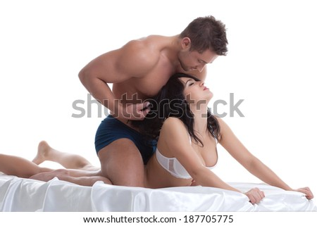 Foreplay of young lovers lying in bed - stock photo