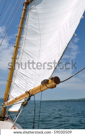 Foresail and Wooden Mast of Schooner Sailboat on a Sunny Summer Day - stock photo