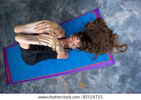Foreshortened view looking down on attractive long haired woman on yoga mat stretching hamstrings in studio against a mottled background. - stock photo