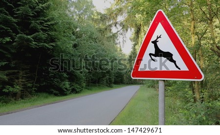 """forest and road signs at roadside """"animal crossing"""" - stock photo"""