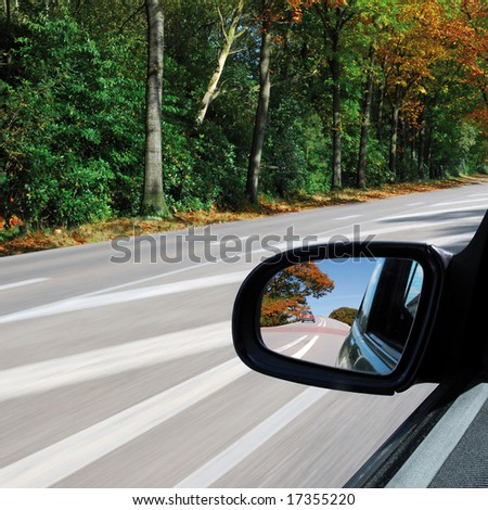 Forest autumn landscape in the sideview mirror of a speeding car on square background - stock photo