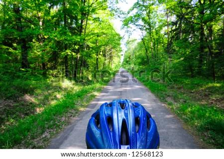 Forest bike path seen over the helmet of a biker. - stock photo