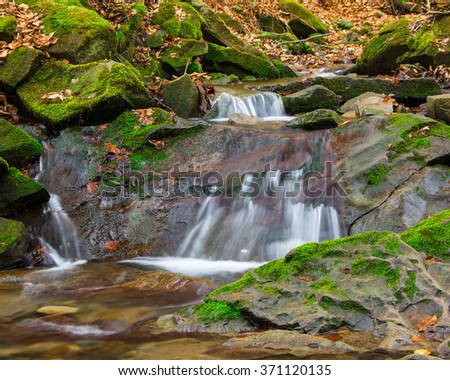 Forest brook waterfall between mossy rocks - stock photo