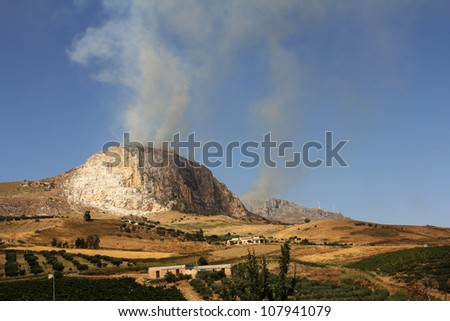Forest fire on the mountain that threatens crops and residential areas - stock photo